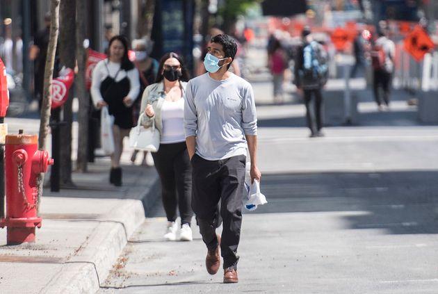 Des piétons marchent sur la rue Sainte-Catherine à Montréal, le samedi 30 mai