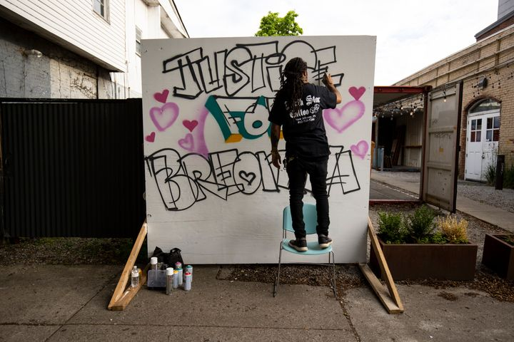 Grafitti artist Resko paints a mural near where a protest march started on May 29 in Louisville, Kentucky.