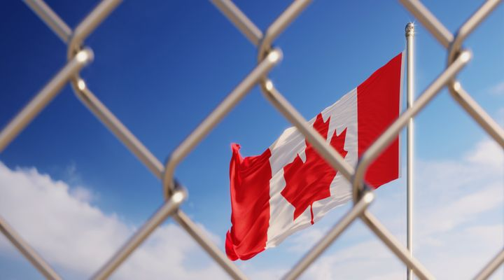 Fence in front of Canadian flag. Illegal immigration concept. Horizontal composition with copy space.