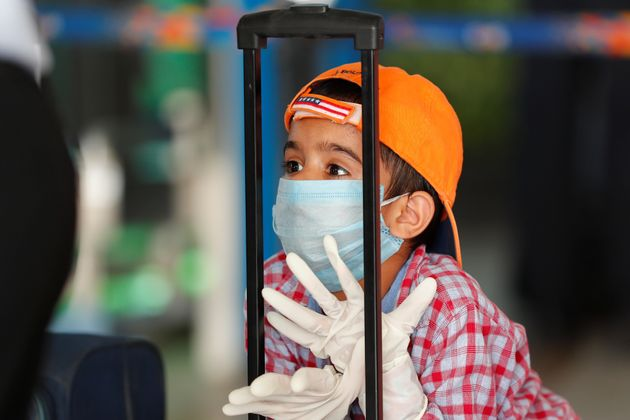 A child wearing a protection mask and gloves is seen at Indira Gandhi International airport on May 25,