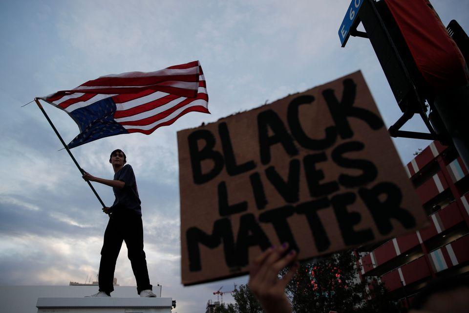 Λας Βέγκας: Ένας λευκός ανεμίζει τη σημαία των ΗΠΑ αναποδογυρισμένη σε διαδήλωση για τον Φλόιντ ενώ ένα πλακάτ δίπλα του γράφει