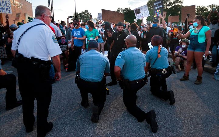 Police officers from Ferguson, Missouri, join protesters to remember George Floyd by taking a knee in the parking lot of the