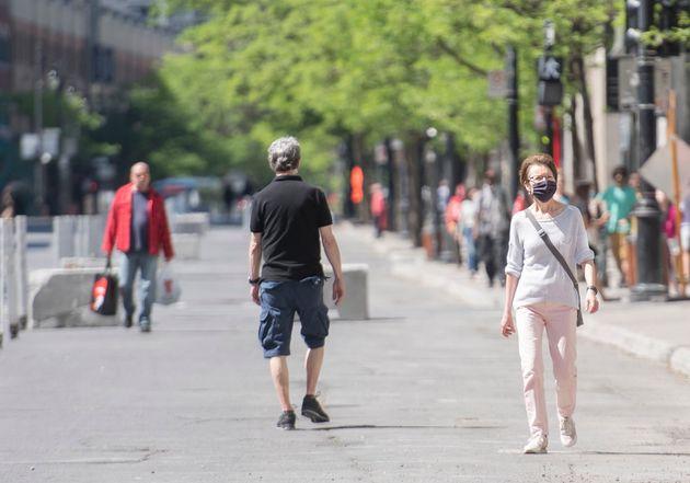 Des piétons marchent sur le trottoir élargi de la rue Sainte-Catherine à Montréal, le samedi 30 mai 2020...