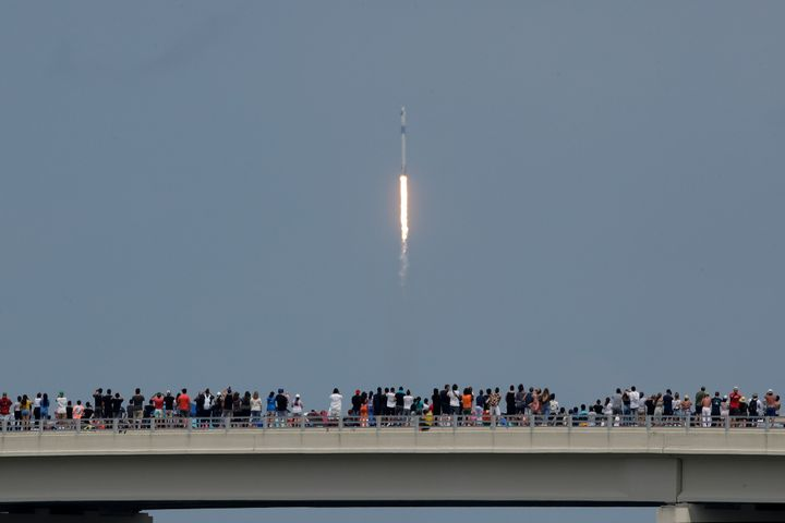 Spectators watch from a bridge in Titusville, Fla. as SpaceX Falcon 9 lifts off with two NASA astronauts on Saturday.