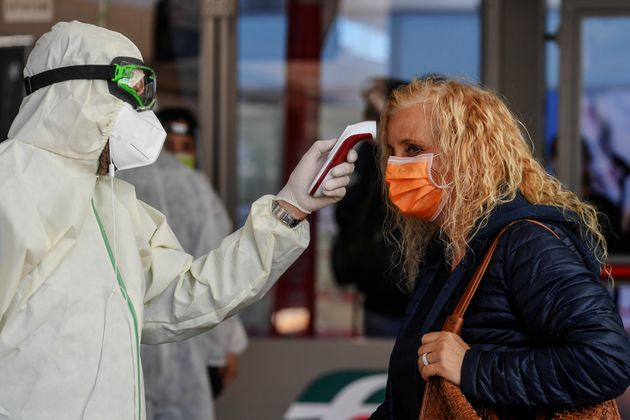 NAPLES, CAMPANIA, ITALY - 2020/05/04: A doctor checks the temperature of a passenger wearing a protective...