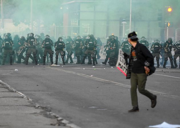 epa08455579 Minnesota State Troopers in riot gear advance in clouds of tear gas towards protesters as...