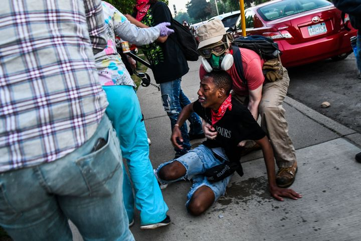 A protestor is assisted by medic protestors after being hit by tear gas near the 5th police precinct during a demonstration to call for justice for George Floyd, a Black man who died while in custody of the Minneapolis police, on May 30, 2020 in Minneapolis, Minnesota. (Photo by CHANDAN KHANNA/AFP via Getty Images)