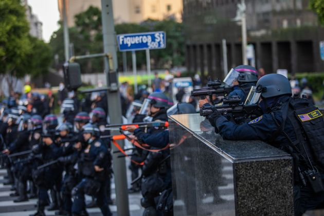 Police officers take position to shoot tear gas at demonstrators in downtown Los Angeles on