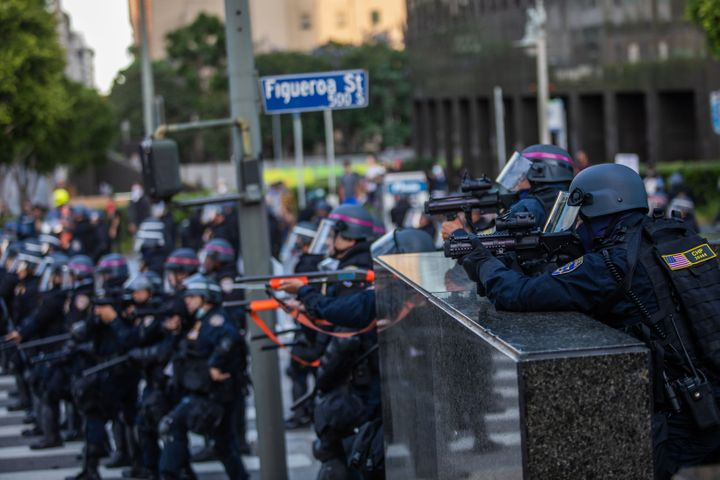 Police officers take position to shoot tear gas at demonstrators in downtown Los Angeles on Saturday.