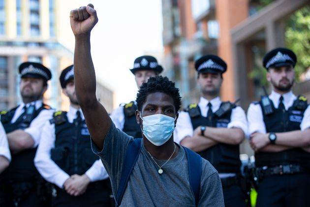 Police officers block a road close to the U.S. Embassy in London, where protesters gathered in support...