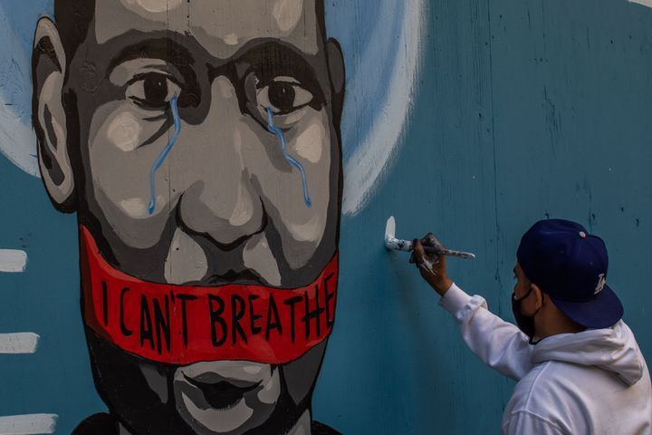 The artist Celos paints a mural in Downtown Los Angeles on May 30, 2020 in protest against the death of George Floyd.
