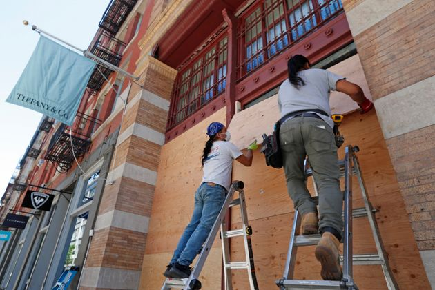 Workers board up the windows of a Tiffany's store in SoHo, New York City, on