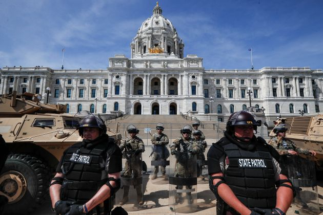 National Guardsmen and Minnesota state police form a barricade as protesters gather outside the Minnesota...