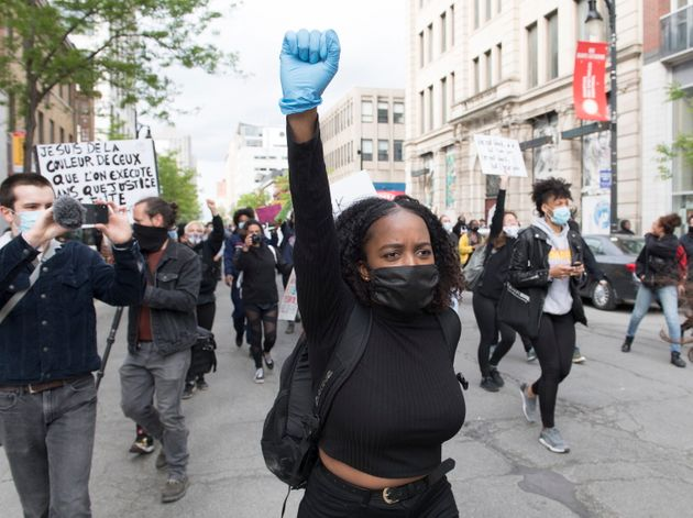 A woman raises her fist during the Montreal protest calling for justice for George Floyd on May 31,