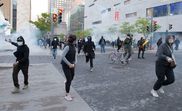 People flee as police disperse tear gas during a demonstration Montreal on May 31,