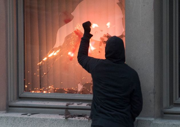 A protester puts a flare through a window during a demonstration calling for justice in the death of...
