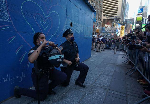 5月31日にニューヨーク・タイムズスクエアで行われた抗議活動の間、片膝をつくニューヨーク市警の警察官