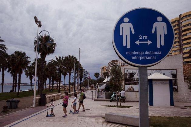 Una familia en el paseo marítimo de la Malagueta (Málaga) ante un disco que recuerda mantener...