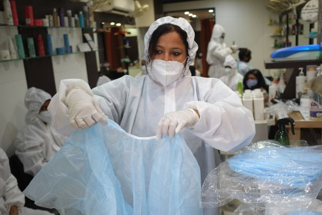 Women hairdressers working in a parlour were seen performing their duties wearing PPE suits along with...