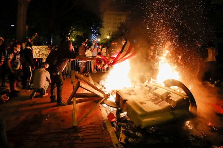 Demonstrators start a fire as they protest the death of George Floyd near the White House in Washington, D.C. on Sunday night