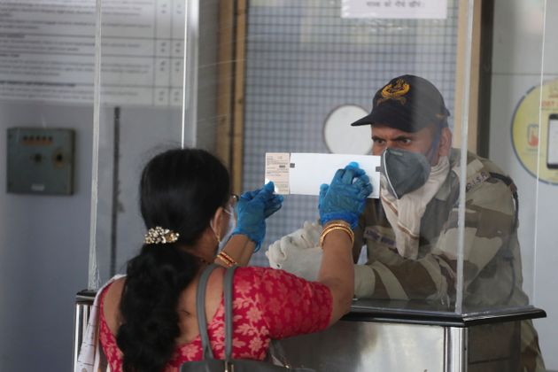 A passenger shows her ticket and identity card to a security personal at the airport in Ahmedabad on...
