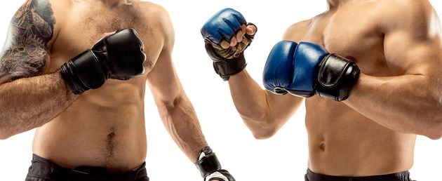 Seconds before war. Two professional fighters posing isolated on white studio background. Couple of fit...