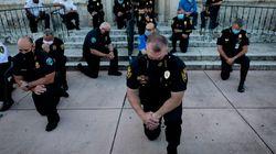 La solidarietà di parte della polizia, in ginocchio per George