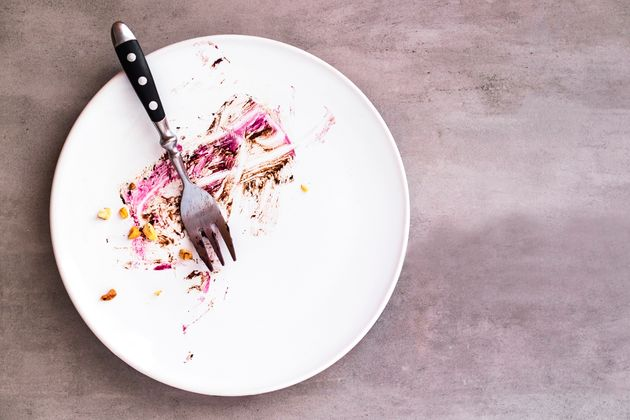 White empty plate with piece of cake leftovers from above on gray background. Copyspace for