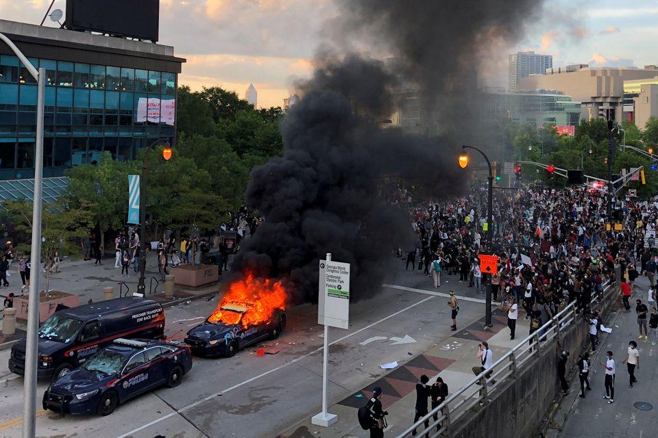 An Atlanta Police car burns as people protest near CNN Center in