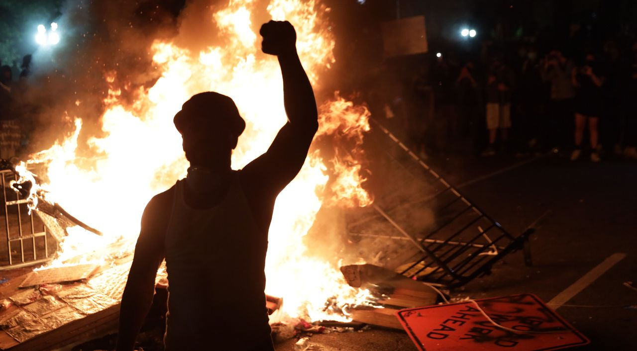 Demonstrators stand around a fire during a protest on May 31 near the White House in response to the killing of George Floyd.