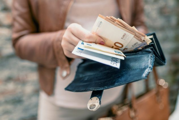 Woman holding in hands wallet with euro money. City girl is taking out money from