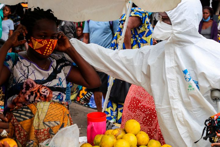 A street shop-keeper is receiving a face mask as a preventive measure against the spread of the COVID-19 coronavirus from a F