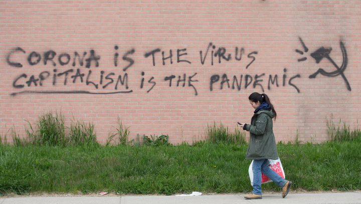 A woman walks by a message scrawled on the side of a Toronto business on May 14, 2020.
