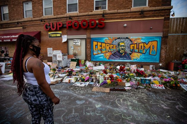A woman pays her respects at the makeshift memorial and mural outside Cup Foods in Minneapolis on May