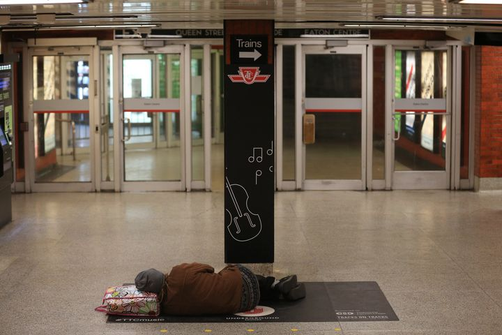 A person sleeps at a Toronto subway station on April 13, 2020.