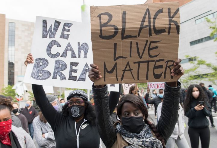 People hold up signs during a demonstration where they called for justice for George Floyd and all victims of police brutality in Montreal on May 31, 2020.