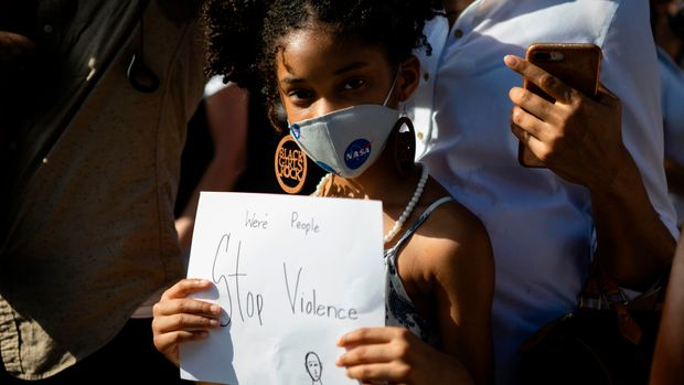 "A young girl wearing a facemask holds a sign during a rally in Coral Gables, Florida on May 30, 2020 in response to the recent death of George Floyd, an unarmed black man who died while being arrested and pinned to the ground by a Minneapolis police officer. - Clashes broke out and major cities imposed curfews as America began another night of unrest Saturday with angry demonstrators ignoring warnings from President Donald Trump that his government would stop violent protests over police brutality ""cold."" (Photo by Eva Marie UZCATEGUI / AFP) (Photo by EVA MARIE UZCATEGUI/AFP via Getty Images)"