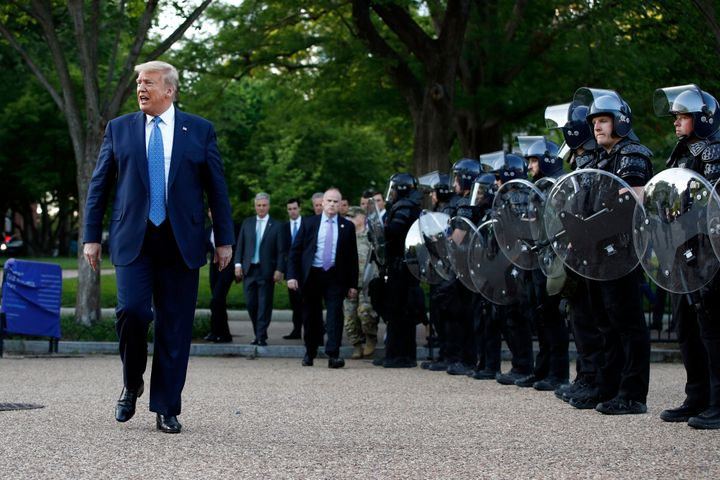 President Donald Trump walks past police in riot gear in Lafayette Park after he stood for photos Monday in front of St. John