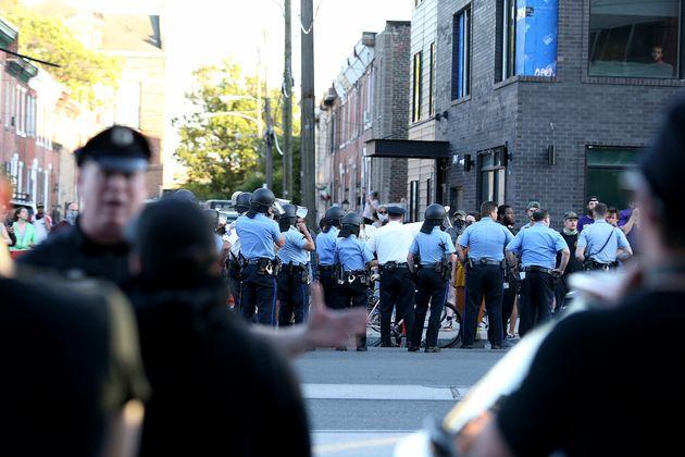 경찰이 사진 뒷쪽(길 건너편)에 모여있는 무리들과 대화를 하고 있다. 대부분 백인 남성으로 구성된 이들은 야구방망이와 해머, 도끼 등을 소지하고 있었다. 필라델피아, 펜실베이니아주....