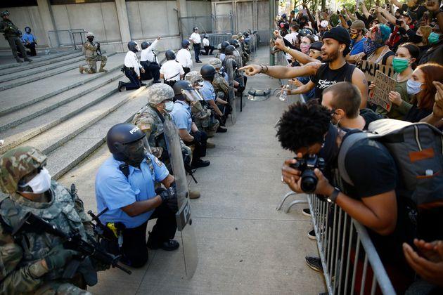 필라델피아 경찰청사 앞에서 필라델피아 경찰과 주방위군이 필라델피아경찰 부청장(사진에 없음)의 제안에 따라 시위대 앞에서 무릎을 꿇고 있다.필라델피아, 펜실베이니아주. 2020년