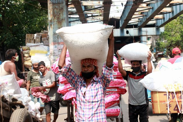 Workers carry sacks filled with sugar to load them onto a supply truck at a wholesale market after the...