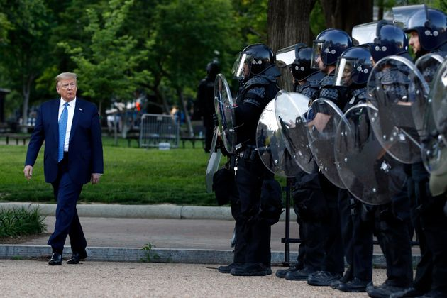 President Donald Trump walks past police in Lafayette Park after he visited outside St. John's Church...