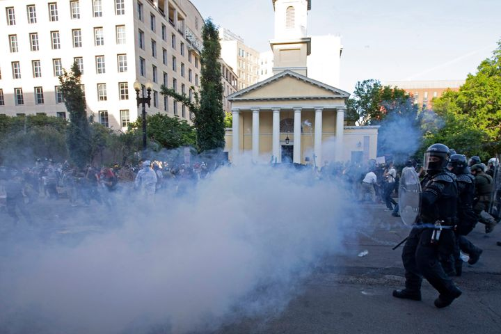 Police officers wearing riot gear push back demonstrators shooting tear gas next to St. John's Episcopal Church outside of the White House, June 1, 2020 in Washington D.C., during a protest over the death of George Floyd.