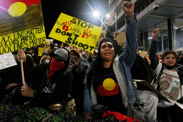 Protestors chant and bend down on their knees in Martin Place during a 'Black Lives Matter' rally on June 02, 2020 in Sydney, Australia.