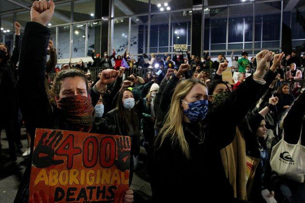 Protestors chant and bend down on their knees in Martin Place during a 'Black Lives Matter' rally on...