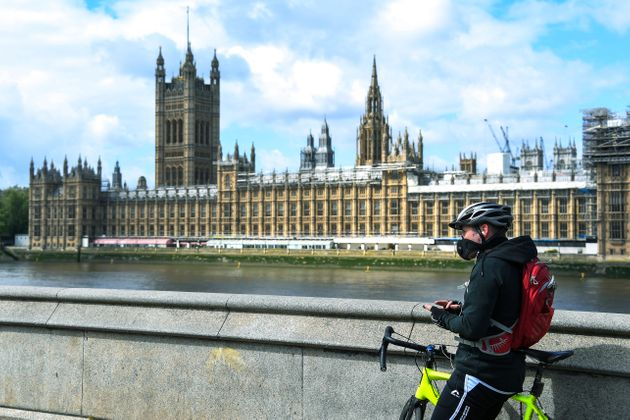 In this file photo dated Friday, May 1, 2020, a man stands with his bike, wearing a protective mask to...