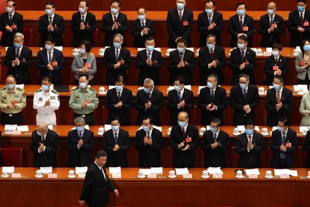 Delegates applaud as Chinese President Xi Jinping arrives for the opening session of China's National...