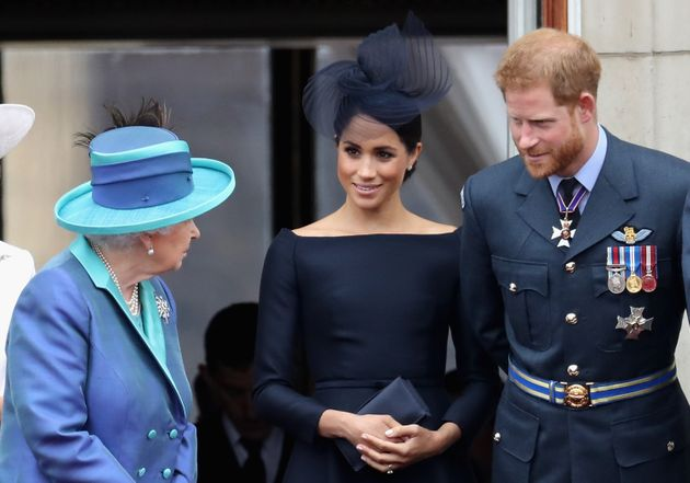 Queen Elizabeth II and the Duke and Duchess of Sussex chat on the balcony of Buckingham Palace on July...