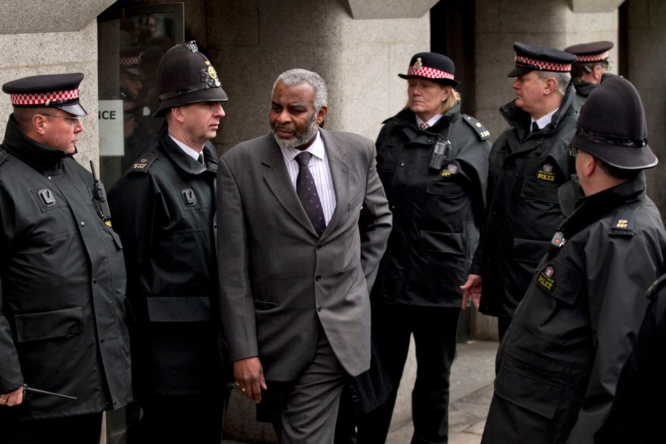 Neville Lawrence, centre, the father of murdered black teenager Stephen Lawrence, walks through police...