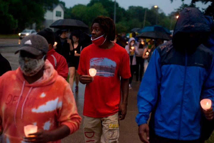 People in Houston march as they mourn the death of George Floyd during a candlelight vigil at Resurrection Metropolitan Commu